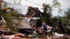 People collect personal effects from damaged homes following a tornado in Dunrobin, Ontario west of Ottawa on Friday, Sept. 21, 2018. A tornado damaged cars in Gatineau, Quebec, and houses in a community west of Ottawa on Friday afternoon as much of southern Ontario saw severe thunderstorms and high wind gusts, Environment Canada said. (Sean Kilpatrick/The Canadian Press via AP)