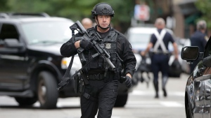A Boston police special operations law enforcement officer carries an assault-style rifle near where police say an officer was shot, Sunday, Sept. 23, 2018, in Boston's South End neighborhood.  (AP Photo/Steven Senne)