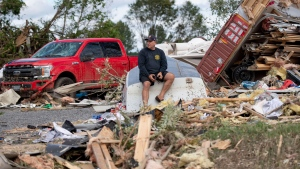 Brian Lowden sits on an overturned boat in his backyard among debris left by a tornado, in Dunrobin, Ont., west of Ottawa, on Sunday, Sept. 23, 2018. The storm tore roofs off of homes, overturned cars and felled power lines in the Ottawa community of Dunrobin and in Gatineau, Que. THE CANADIAN PRESS/Justin Tang