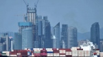 In this Sept. 13, 2018, photo, a container ship sails past the city skyline of Qingdao in eastern China's Shandong province. China raised tariffs Monday, SEPT. 24 on thousands of U.S. goods in an escalation of its fight with President Donald Trump over technology policy and accused Washington of bullying Beijing and damaging the global economy. (Chinatopix via AP)
