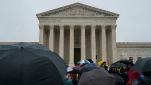 Protesters gather in the rain in front of the Supreme Court on Capitol Hill in Washington, Monday, Sept. 24, 2018. (AP Photo/Carolyn Kaster)