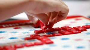 "This May 16, 2015 photo released by Hasbro shows a contestant competing in the first round of the 2015 North American School Scrabble Championship at Hasbro headquarters in Pawtucket, R.I. Merriam-Webster released the sixth edition of ""The Official Scrabble Players Dictionary"" early Monday with more than 300 additions. (Stew Milne/Hasbro via AP)"