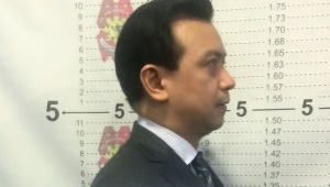 In this photo provided by the Philippine National Police Makati, Philippine opposition Sen. Antonio Trillanes IV for his mugshot inside a police station in Makati, metropolitan Manila after the Makati Regional Trial Court Branch 150 issued an order for his arrest Tuesday, Sept. 25, 2018. A Philippine court ordered Trillanes arrested Tuesday after the president revoked the senator's 2011 amnesty for a failed coup attempt and revived rebellion charges against him in an unprecedented legal move the legislator called a blow to democracy. Trillanes later posted bail. (Philippine National Police Makati via AP)