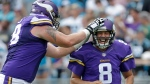 In this Sept. 25, 2016, file photo, Minnesota Vikings' Sam Bradford (8) is congratulated by Jeremiah Sirles (78) after touchdown pass against the Carolina Panthers in the second half of an NFL football game in Charlotte, N.C. (AP Photo/Bob Leverone, File)