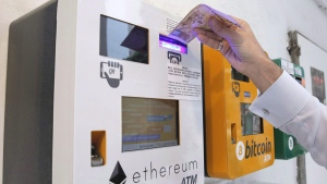A man uses the Ethereum ATM, beside a Bitcoin ATM, in Hong Kong on May 11, 2018. THE CANADIAN PRESS/AP, Kin Cheung