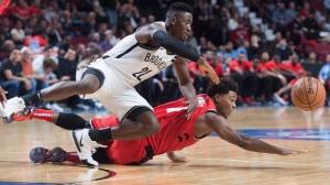 Toronto Raptors' Kyle Lowry, right, and Brooklyn Nets' Caris LeVert dive for the ball during second half NBA pre-season basketball action in Montreal, Wednesday, October 10, 2018. THE CANADIAN PRESS/Graham Hughes
