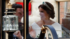 Britain's Princess Eugenie of York, right, and her husband Jack Brooksban travel in the Scottish State Coach following their wedding at St George's Chapel, Windsor Castle, near London, England, Friday Oct. 12, 2018. (Adrian Dennis/Pool via AP)