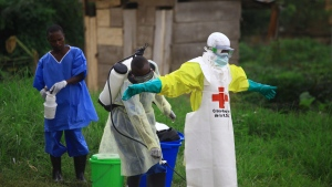 In this Sept. 9, 2018, file photo, a health worker sprays disinfectant on his colleague after working at an Ebola treatment center in Beni, Eastern Congo. (AP Photo/Al-hadji Kudra Maliro, File)