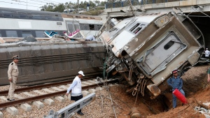 Police officer and train workers stand by a derailed train Tuesday Oct.16, 2018 near Sidi Bouknadel, Morocco. A shuttle train linking the Moroccan capital Rabat to a town further north on the Atlantic coast derailed Tuesday, killing several people and injuring dozens, Moroccan authorities and the state news agency said. (AP Photo/Abdeljalil Bounhar)