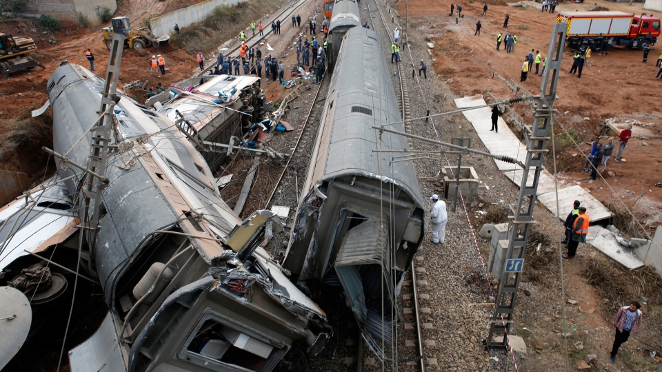 People gather after train derailed Tuesday Oct.16, 2018 near Sidi Bouknadel, Morocco. A shuttle train linking the Moroccan capital Rabat to a town further north on the Atlantic coast derailed Tuesday, killing several people and injuring dozens, Moroccan authorities and the state news agency said. (AP Photo/Abdeljalil Bounhar)