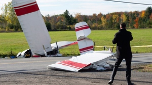 A reporter looks at the crash site of a plane in a ditch near Carp, Ont., west of Ottawa, Tuesday, October 16, 2018. THE CANADIAN PRESS/Adrian Wyld