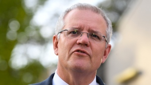 Australian Prime Minister Scott Morrison speaks to the media after a visiting the Piallago Estate smokehouse in Canberra, Wednesday, Oct. 17, 2018. Morrison signaled that he could accept New Zealand's longstanding offer to resettle 150 refugees exiled to Pacific islands as long as the Australian Parliament legislates to ban them from ever setting foot in Australia. (Lukas Coch/AAP Image via AP)