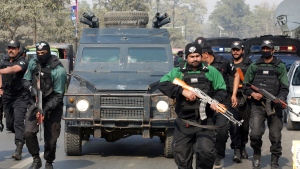 FILE-- In this Feb. 7, 2018, file photo, Pakistani police commandos escort a police van carrying Mohammad Imran, who is accused of the brutal killings of eight children in the eastern city of Kasur, as it arrives at an anti-terrorist court, in Lahore, Pakistan. The serial killer of eight children was executed at a Pakistani prison Wednesday morning, Oct. 17, 2018, after the country's top court rejected a request for his public hanging, officials said. (AP Photo/K.M. Chaudary, File)