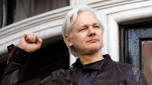 FILE - In this file photo dated Friday May 19, 2017, WikiLeaks founder Julian Assange looks out from the balcony of the Ecuadorian embassy in London. (AP Photo/Matt Dunham, FILE)