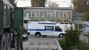 Police vehicles are parked near a vocational college in Kerch, Crimea, Thursday, Oct. 18, 2018. An 18-year-old student strode into his vocational school in Crimea, a hoodie covering his blond hair, then pulled out a shotgun and opened fire on Wednesday, killing scores of students and wounding dozens of others before killing himself. (AP Photo/Sergei Demidov)