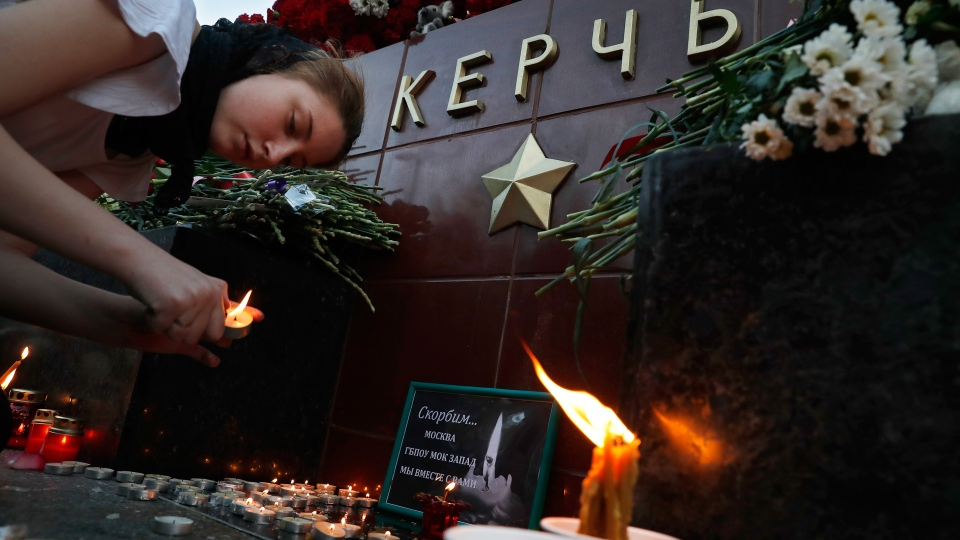 A girl lights a candle in memory of the victims of Wednesday's attack on a vocational college in Kerch, Crimea, at the memorial stone with the word Kerch in the Alexander Garden near the Kremlin, Moscow, Russia, Thursday, Oct. 18, 2018. (AP Photo/Pavel Golovkin)