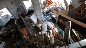 Amy Hay, an employee of the the Driftwood Inn for 18 years, sifts through debris for valuables in the aftermath of Hurricane Michael in Mexico Beach, Fla., Wednesday, Oct. 17, 2018. (AP Photo/Gerald Herbert)