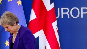 British Prime Minister Theresa May walks off the podium after a media conference during an EU summit in Brussels, Thursday, Oct. 18, 2018. Thousands of protesters were gathering in central London on Saturday to call for a second referendum on Britain's exit from the European Union. (AP Photo/Alastair Grant)