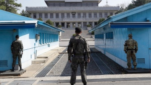 In this April 18, 2018 file photo, two South Korean soldiers, center and left, and U.S. soldier, right, stand in the southern side during a press tour at the border village of Panmunjom in the Demilitarized Zone, South Korea. (AP Photo/Lee Jin-man, File)
