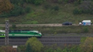 A GO train and an ambulance are seen on the Lakeshore West line east of Bronte station on Oct. 19, 2018. (Chopper 24)