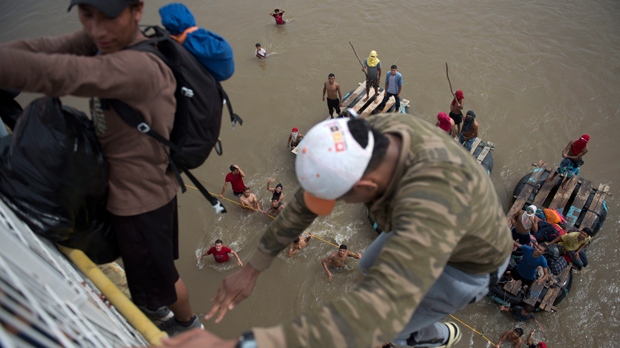 Migrants tired of waiting to cross into Mexico, jumped from a border bridge fence into the Suchiate River, in Tecun Uman, Guatemala, Friday, Oct. 19, 2018. Some of the migrants traveling in a mass caravan towards the U.S.-Mexico border organized a rope brigade to ford its muddy waters. (AP Photo/Oliver de Ros)