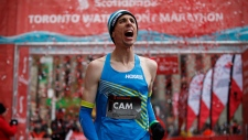 Canadian Cam Levins reacts as he crosses the finish line of the Toronto Scotiabank Waterfront Marathon in Toronto on Sunday, Oct. 21, 2018. THE CANADIAN PRESS/Cole Burston