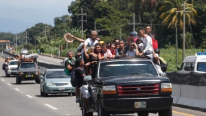 Central American migrants making their way to the U.S. in a large caravan fill the truck of a driver who offered them the free ride, as they arrive to Tapachula, Mexico, Sunday, Oct. 21, 2018. (AP Photo/Moises Castillo)