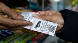 A lottery player buys Mega Millions lottery tickets at a news stand in Philadelphia, Monday, Oct. 22, 2018. No one won the $1 billion jackpot in Saturday night's drawing, which means the top prize for Tuesday night's Mega Millions drawing would be the largest lottery jackpot in U.S. history. (AP Photo/Matt Rourke)