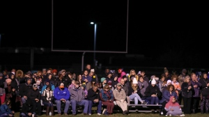 People attend a gathering during a moment of silence for Jayme Closs at the Barron High School Football Stadium in Barron, Wis., Monday, Oct. 22, 2018. Authorities revealed they're looking for two vehicles in connection with the disappearance of the Wisconsin girl whose parents were gunned down last week, calling on hundreds of volunteers to resume a ground search. State, local and federal investigators have been searching for Closs since early Oct. 15, when deputies discovered someone had broken into the family's rural Barron home and shot her parents to death. (Jerry Holt/Star Tribune via AP)