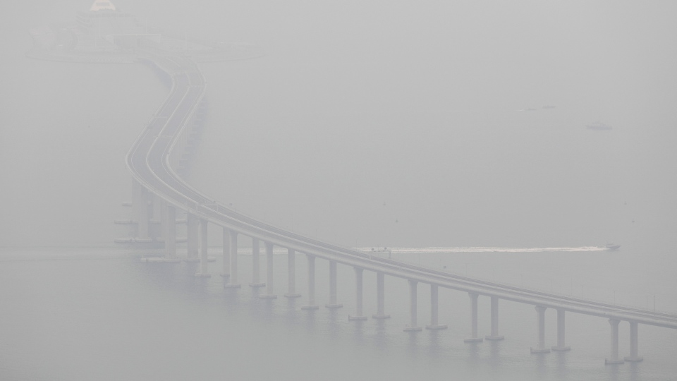 A police speed boat sails through the China-Zhuhai-Macau-Hong Kong Bridge in heavy fog in Hong Kong Tuesday, Oct. 23, 2018. The world's longest cross-sea project, which has a total length of 55 kilometers (34 miles) is official opened by Chinese President Xi Jinping on Tuesday. (AP Photo/Vincent Yu)