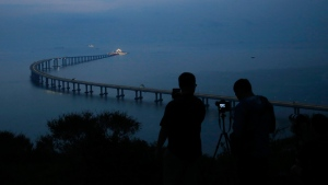 Photojournalists take photos of the Hong Kong-Zhuhai-Macau Bridge in Hong Kong, Monday, Oct. 22, 2018. (AP Photo/Kin Cheung)