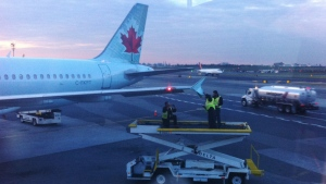 Runway crew members examine the wing tip of an Air Canada plane which arrived at LaGuardia Airport in New York on Monday, Oct. 22, 2018. An Air Canada flight that had just landed at New York's LaGuardia Airport late Monday afternoon was damaged as it sat on the taxiway by another passing plane. New York Port Authority spokesman Rudy King says the Air Canada jet was stationary on the taxiway when an American Airlines plane that was attempting to turn clipped its wing. THE CANADIAN PRESS/HO - Tim Clark