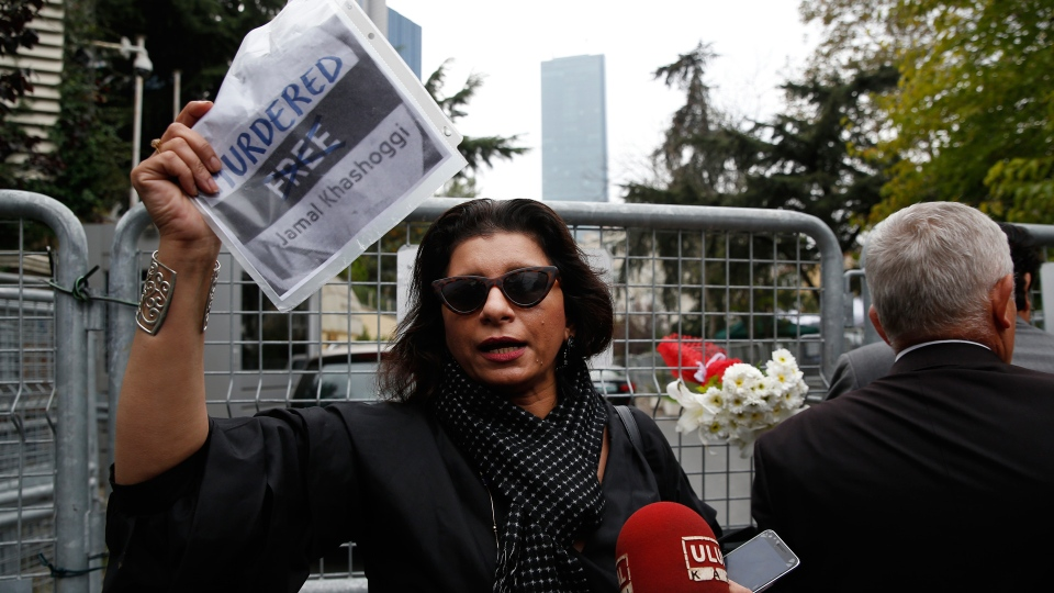 Sahar Zeki, an activist and a friend of slain Saudi writer Jamal Khashoggi, holds a picture of him after attaching a bouquet of flowers on the barriers blocking the road leading to Saudi Arabia's consulate in Istanbul, Tuesday, Oct. 23, 2018. (AP Photo/Lefteris Pitarakis)