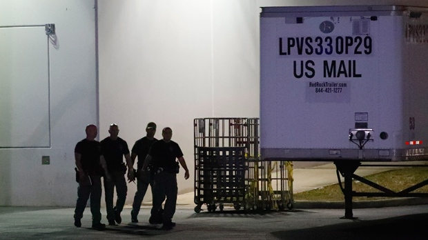 Members of the Miami-Dade County Bomb Squad walk outside a postal facility, Thursday, Oct. 25, 2018, in Opa-Locka, Fla. Investigators searched coast-to-coast Thursday for the culprit and motives behind the bizarre mail-bomb plot aimed at critics of the president. (AP Photo/Wilfredo Lee)