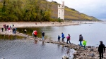 In this Wednesday, Oct.24, 2018 picture people walk over stones looking out of the river Rhine to the Maeuseturm (mice tower) of Bingen, Germany, which usually sits on an island.  A hot, dry summer has left German waterways at record low levels, causing chaos for the inland shipping industry, environmental damage and billions of euros of losses _ a scenario that experts warn could portend things to come as global temperatures rise.  (AP Photo/Michael Probst)