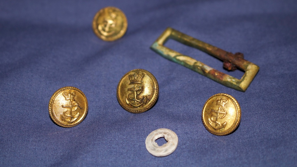 A mother of pearl button, gilt brass buttons and a gilt buckle frame from naval officer's uniform found at a Franklin expedition gravesite are shown in a handout photo. THE CANADIAN PRESS/HO Douglas Stenton-Government of Nunavut