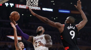 Los Angeles Lakers' LeBron James (23) drives to the basket between Toronto Raptors' Serge Ibaka (9) and Danny Green (14) during the first half of an NBA basketball game Sunday, Nov. 4, 2018, in Los Angeles. (AP Photo/Marcio Jose Sanchez)