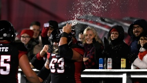 Ottawa Redblacks offensive lineman Jon Gott (63) smashes a beer can on his helmet after chugging it, as he celebrates his team's touchdown against the Toronto Argonauts during second half CFL football action in Ottawa on Friday, Nov. 2, 2018. THE CANADIAN PRESS/Justin Tang
