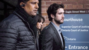 Marco Muzzo, right, leaves the Newmarket courthouse surrounded by family, on February 4, 2016. (THE CANADIAN PRESS/Christopher Katsarov)