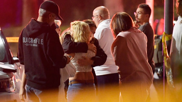"People comfort each other as they stand near the scene Thursday, Nov. 8, 2018, in Thousand Oaks, Calif. where a gunman opened fire Wednesday inside a country dance bar crowded with hundreds of people on ""college night,"" wounding 11 people including a deputy who rushed to the scene. Ventura County sheriff's spokesman says gunman is dead inside the bar. (AP Photo/Mark J. Terrill)"