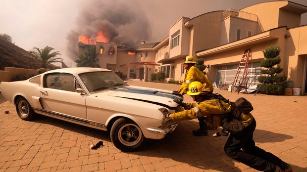 Firefighters push a vehicle from a garage as a wildfire fire burns a home near Malibu Lake in Malibu, Calif., Friday, Nov. 9, 2018. (AP Photo/Ringo H.W. Chiu)