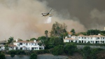 "A helicopter drops water on a brush fire behind homes during the Woolsey Fire in Malibu, Calif., Friday, Nov. 9, 2018. A fast-moving wildfire in Southern California has scorched a historic movie site recently used by the HBO series ""Westworld"" and forced numerous celebrities to join the thousands fleeing flames that have claimed homes and prompted the total evacuation of the celebrity enclave Malibu. (AP Photo/Ringo H.W. Chiu)"