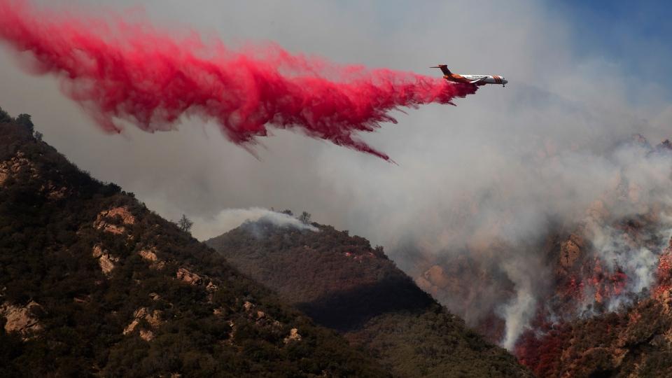 A plane drops fire retardant on a burning hillside Sunday, Nov. 11, 2018, in Malibu, Calif. (AP Photo/Jae C. Hong)