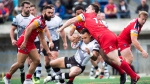 In this file photo, Toronto Wolfpack forward Mason Caton-O'Brien, centre, gets tackled by London Broncos MattyGee, right, during first half rugby league action in Toronto on Sunday, October 7, 2018.  THE CANADIAN PRESS/Nathan Denette