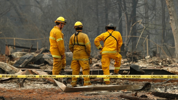 Firefighters stand over human remains found at a burned out home at the Camp Fire, Sunday, Nov. 11, 2018, in Paradise, Calif. (AP Photo/John Locher)