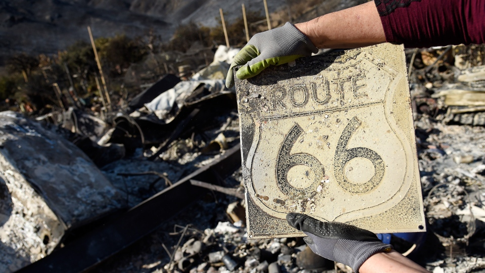 Donna Phillips shows a charred Route 66 sign she found among the possessions of her friend Marsha Maus, Sunday, Nov. 11, 2018, after wildfires tore through the Seminole Springs Mobile Home Park in Agoura Hills, Calif. Maus has been a resident of the neighborhood for 15 years. (AP Photo/Chris Pizzello)