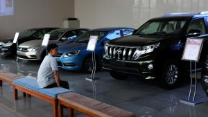 In this July 26, 2018 photo, a man sits at a showroom that sells imported cars in Pyongyang, North Korea. Twenty years after his father almost bargained them away for a pair of nuclear reactors, North Korean leader Kim Jong Un has his nuclear weapons - and a nation still plagued by chronic blackouts. But years of sanctions have spurred the North to cobble together a creative smorgasbord of alternative resources, some off the official grid and some flat-out illegal. (AP Photo/Dita Alangkara)
