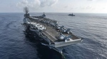 This Aug. 31, 2018, photo released by U.S. Navy, the aircraft carrier USS Ronald Reagan, front, and the guided-missile destroyer USS Milius, center, conduct an exercise with Japan Maritime Self-Defense Force ships off South China Sea. A U.S. Navy warplane belonging to the aircraft career USS Ronald Reagan has crashed into the sea northeast of the Philippines, but its two aviators were safely rescued. The Navy's 7th Fleet said in a statement that the F/A-18 Hornet had a mechanical problem during a routine operations in the Philippine Sea, Monday, Nov. 12, 2018. (Mass Communication Specialist 2nd Class Kaila V. Peters/U.S. Navy via AP)