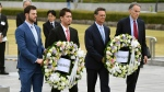 MLB All-Star team, from left, Mitch Haniger of the Seattle Mariners, Kenta Maeda of the Los Angeles Dodgers, and manager Don Mattingly lay a wreath at the cenotaph in the Peace Memorial Park which commemorates the victims of the atomic bombings in 1945, in Hiroshima, western Japan, Monday, Nov. 12, 2018. (Kyodo News via AP)