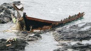 "A wooden boat is left after being washed ashore in Tsuruoka, Yamagata prefecture, northern Japan Monday, Dec. 4, 2017. Coast guard said a Japanese fishing boat picked up a male body floating off the coast of Sakata in the prefecture and two more bodies washed up on a nearby beach an hour and half later. Twenty-eight of the vessels, dubbed ""ghost boats,"" were detected in November, up from just four in November last year. (Kyodo News via AP)"